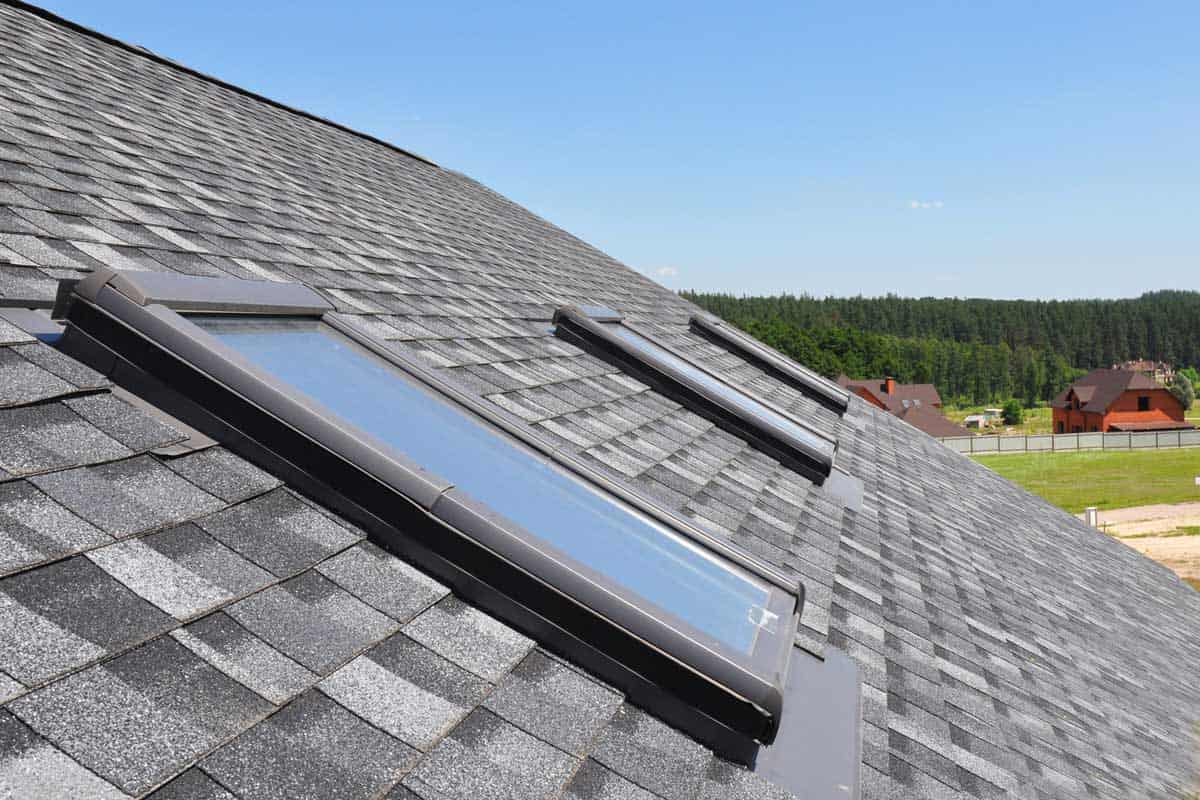 Attic skylight. Asphalt Shingles House Roofing Construction with Attic Roof windows, skylights waterproofing