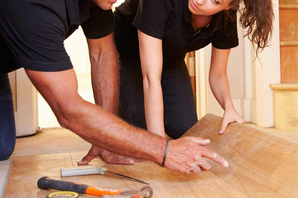 Man and woman laying wood panel flooring in a house, Do You Tip Floor Installers And Refinishers (And How Much)?