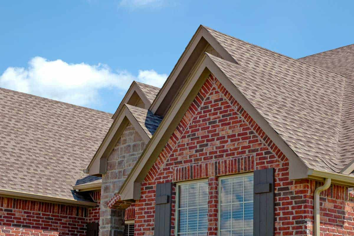 Roof line with asphalt shingles, colored brick house