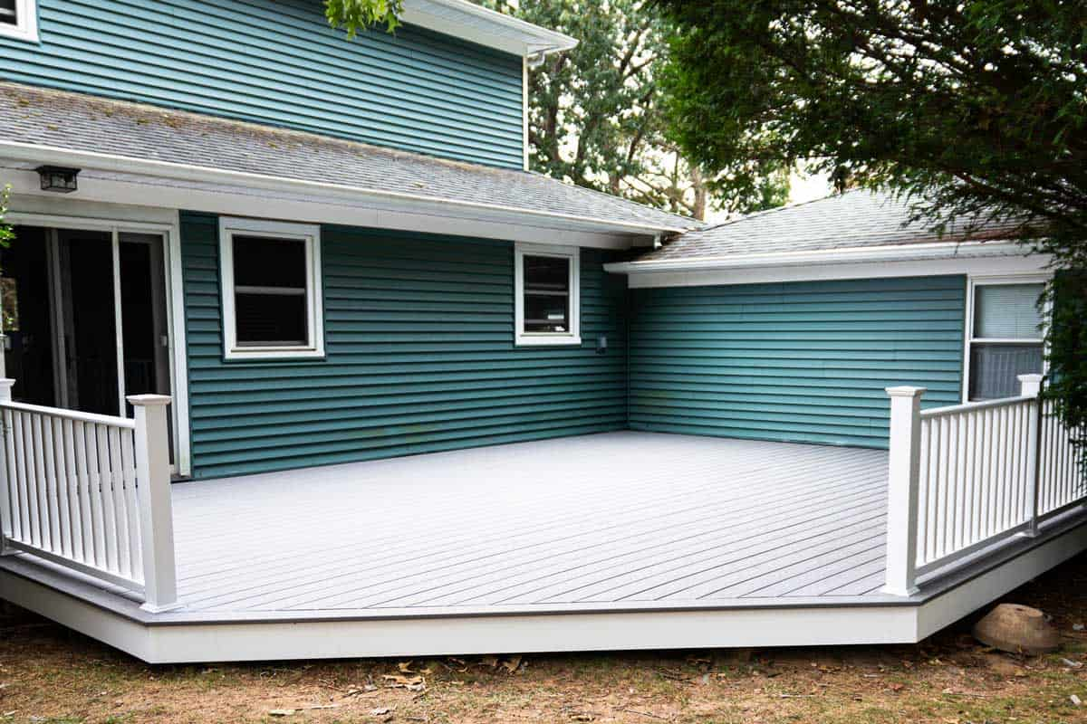 A dark colored vinyl siding and A new deck is installed on the back of a house with composite material and white hand rails