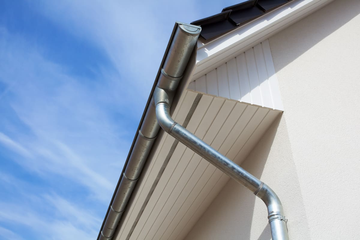 A galvanized iron gutter with a metal downspout on a gable roof design, How Much Does It Cost To Realign Gutters?