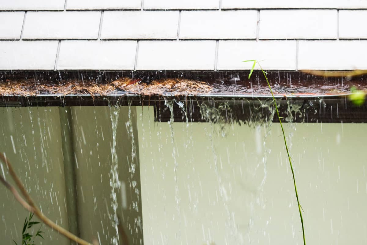 A gutter overflowing due to heavy rain