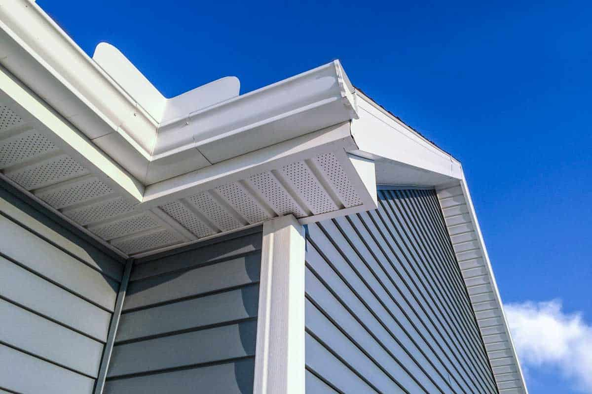 A low angle view of soffit, gutters, downspout and vinyl siding on a new home. Blue sky is in the background, Can Faded Vinyl Siding Be Painted? [3 Things to Consider]