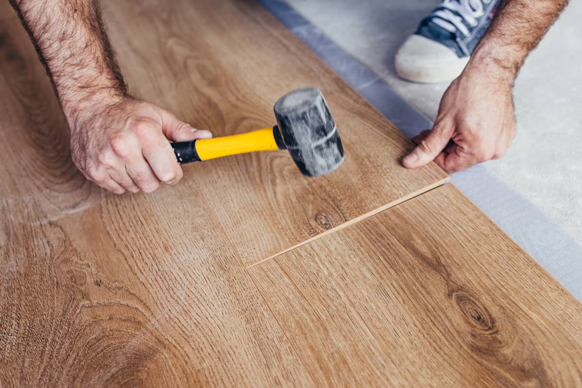 A tile setter using a small mallet to place a vinyl plank flooring, How to Stagger Vinyl Plank Flooring? [3 Steps]