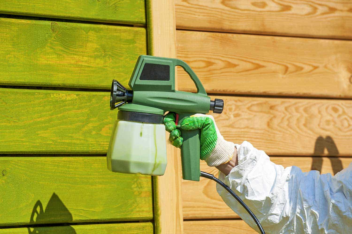 Hand painting wooden wall with spray gun