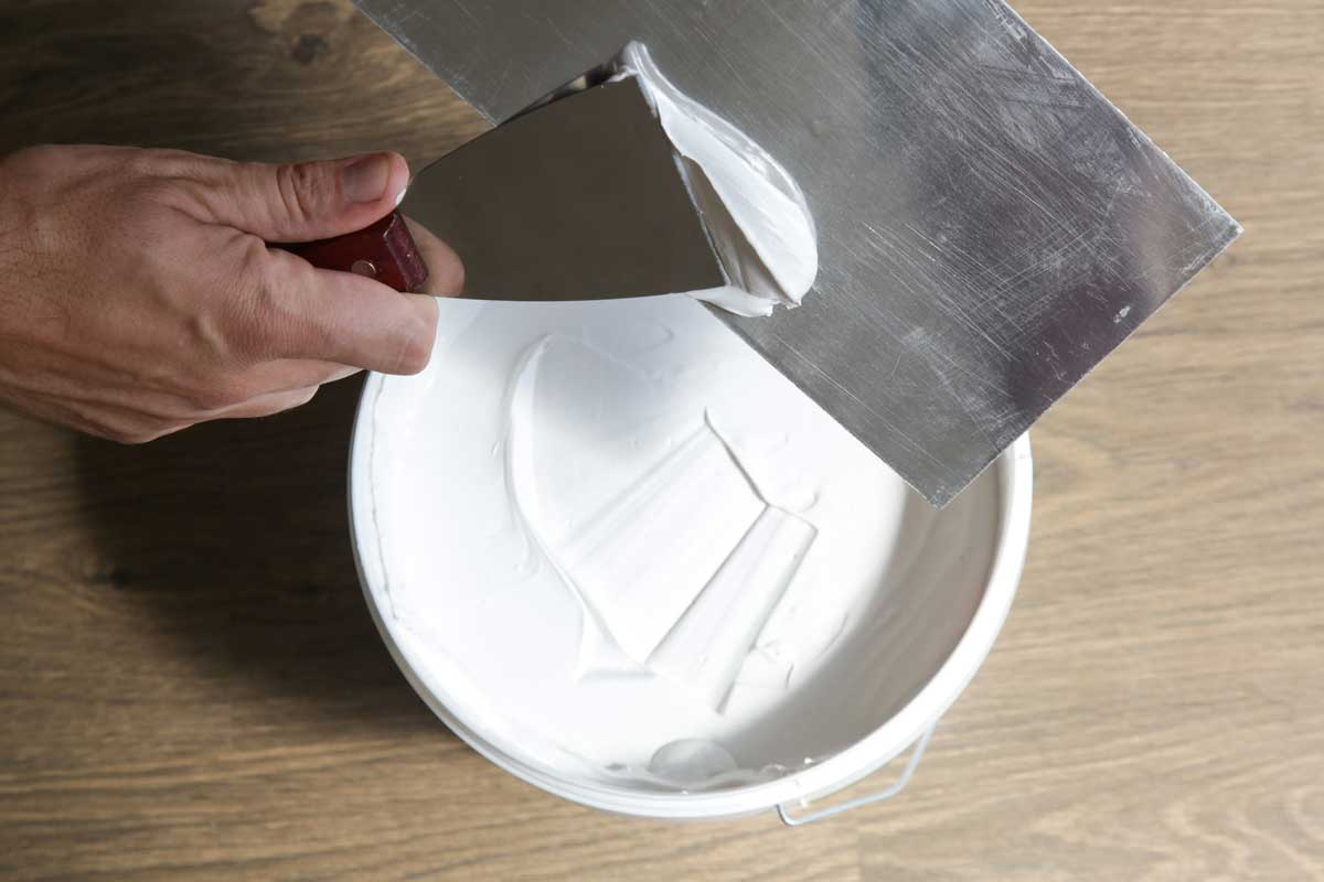 Man plastering ceiling with putty-knife as preparation for painting