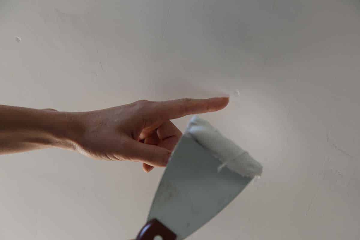Man plastering ceiling with putty-knife, close up image