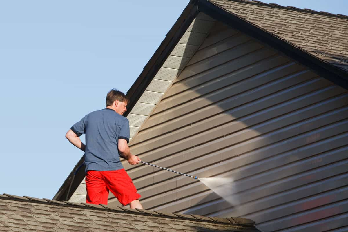 Man using pressure washer to power wash his vinyl siding, Can You Power Wash Vinyl Siding?