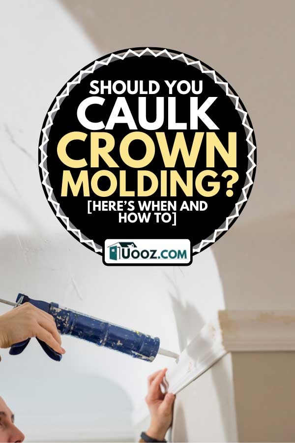A man finishes crown moulding installation with caulk sealant, Should You Caulk Crown Molding? [Here's when and how to]