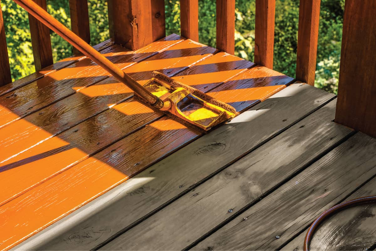 Staining wooden deck with paint roller; untreated patch of wood shown for contrast