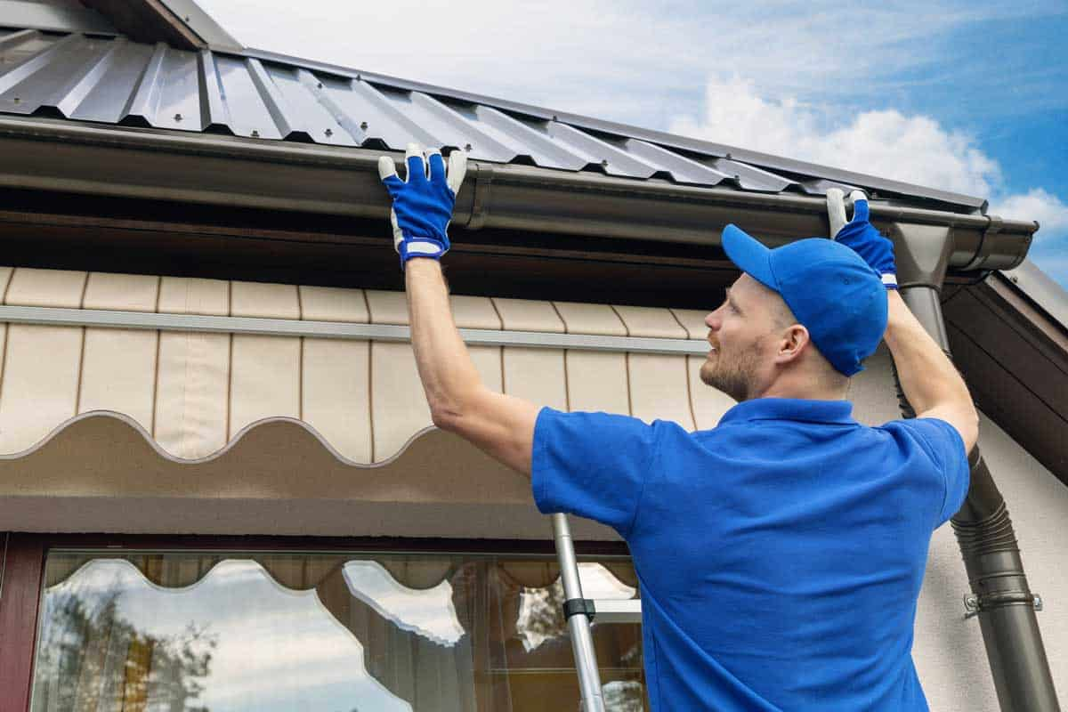 man installing house roof rain gutter system, Are Gutters Hard to Install? [Can This Be Your Next DIY Project?]