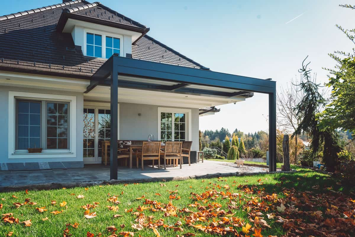 Pre-colonial house with an extended porch with chairs and tables, Do You Need Guttering On A Porch?