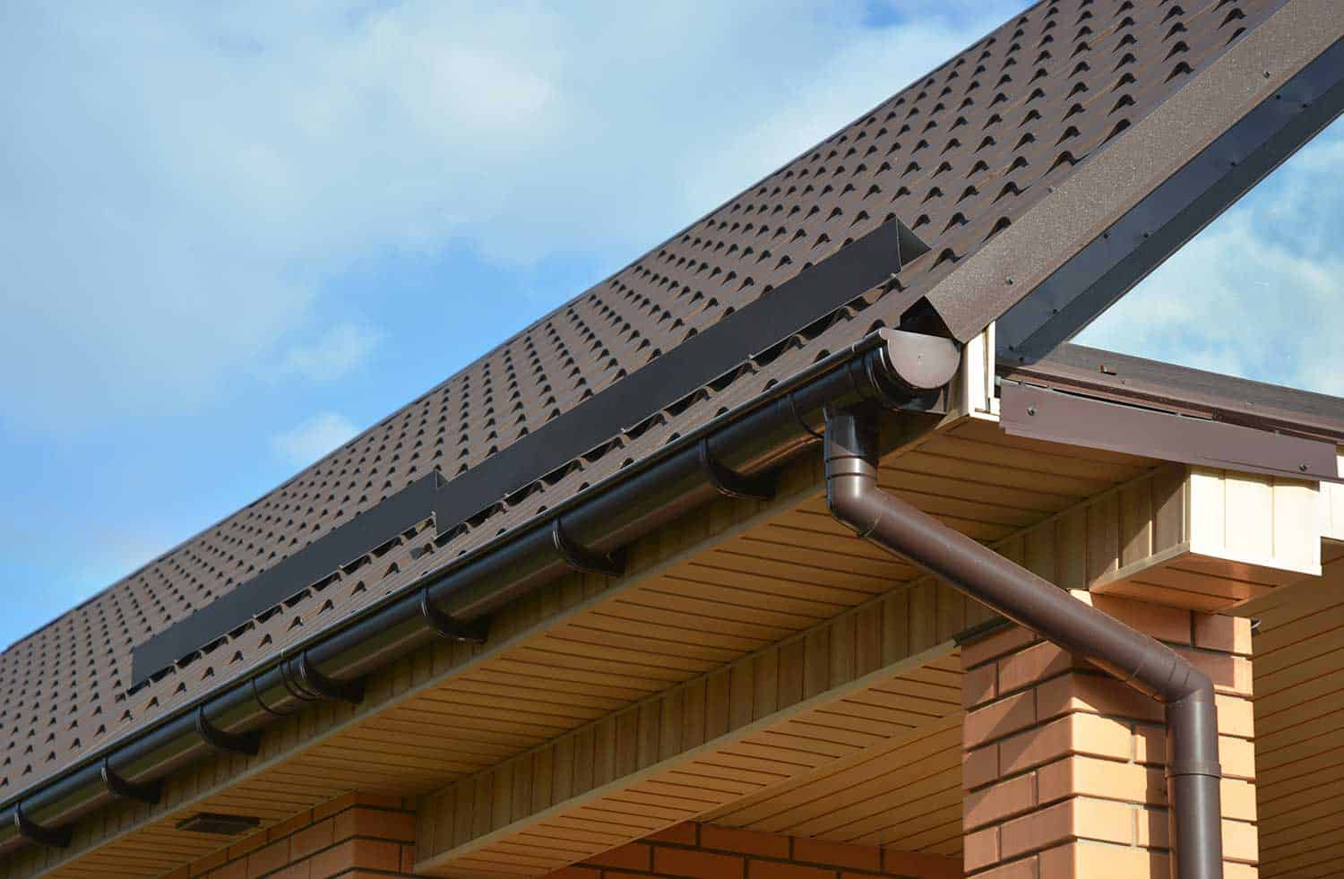 Modern house construction with metal roof corner, rain gutter system and roof protection from snow board