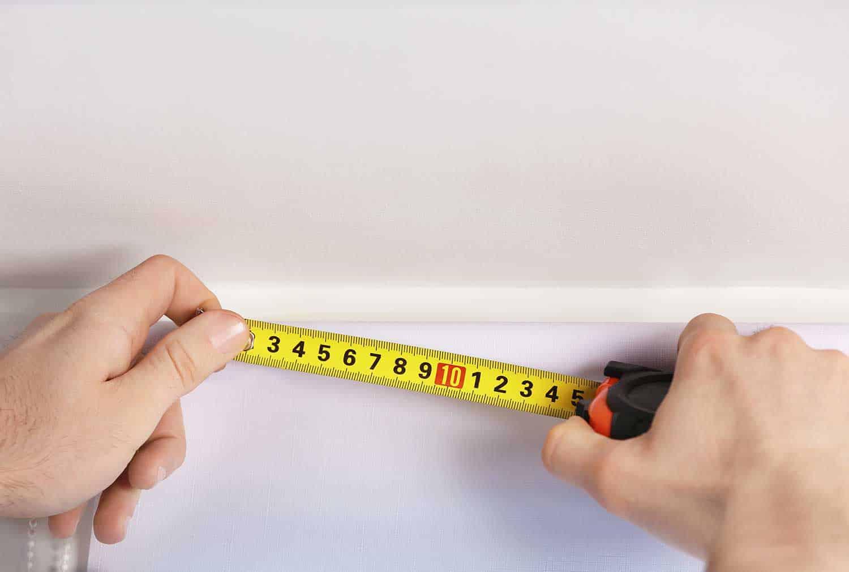 Hands making window measurements