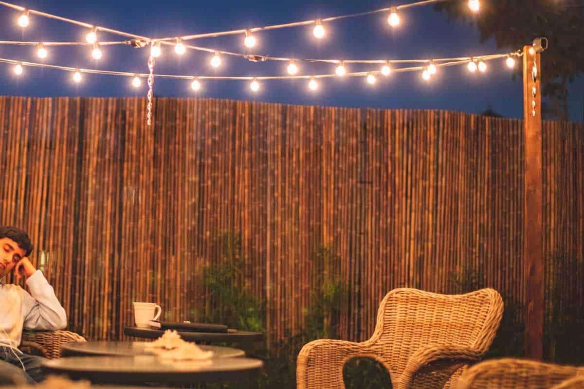 An outdoor patio setup in the gravel backyard garden with bamboo fence