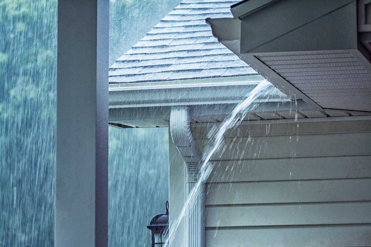 Rain storm water pouring over the overhanging eaves trough aluminum roof gutter system, How To Stop Rain From Overshooting The Gutter?