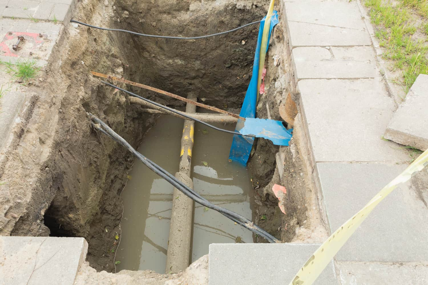 trench water with pipes and wires