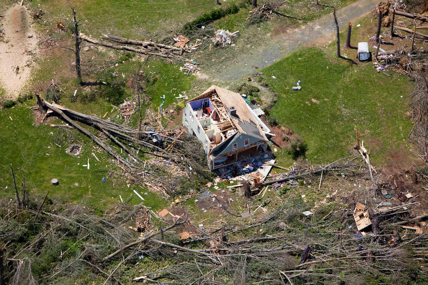 An aerial view of the destruction done by a tornado to a single family house