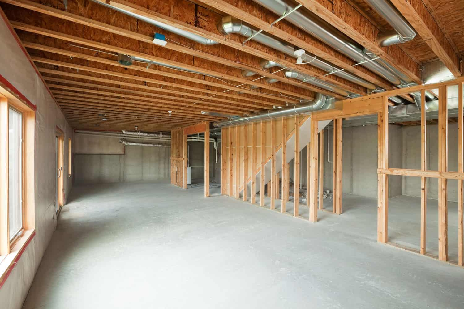 An unfinished walk-out basement in a large two-story or ranch house