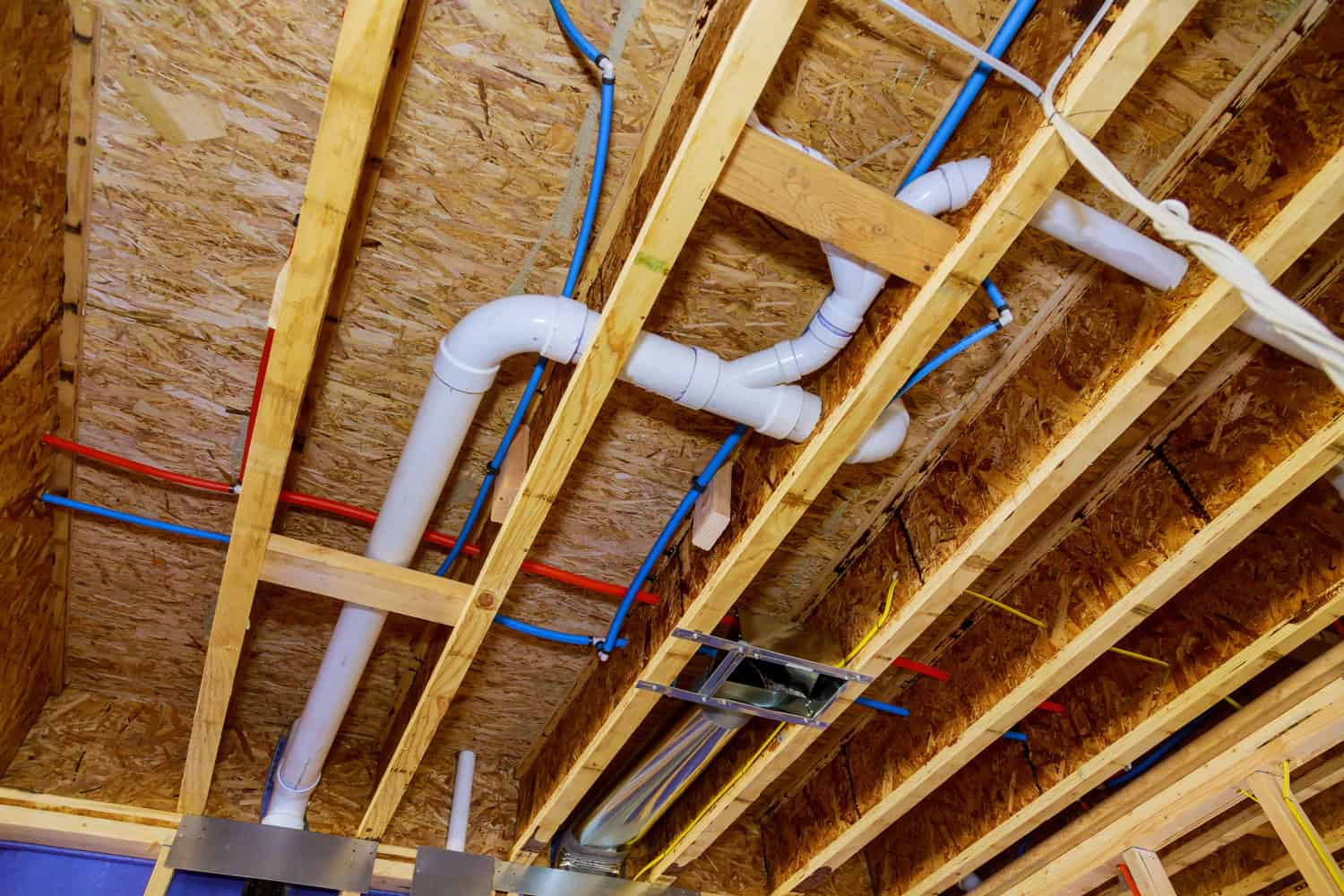 Home construction with hot red and cold blue pex pipe layout in pipes and exposed beams