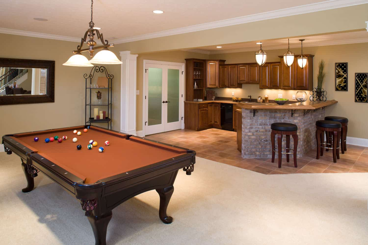 Recently finished residential lower level game room and bar with pool table and stools