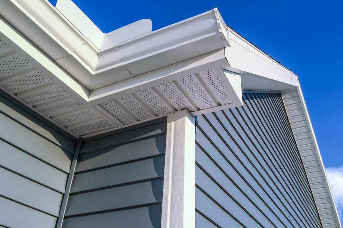 A low angle view of soffit, gutters, downspout and vinyl siding on a new home, How to Fix a Hole in Vinyl Siding [7 Steps]