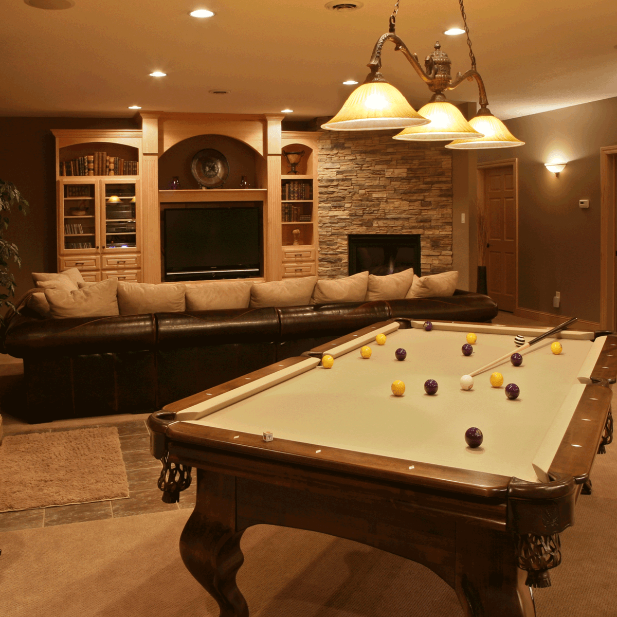 A pool table and entertainment area inside a basement