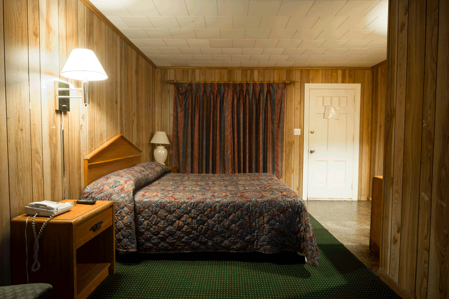 A rustic themed bedroom with basement with a green carpet and properly by wall lamps