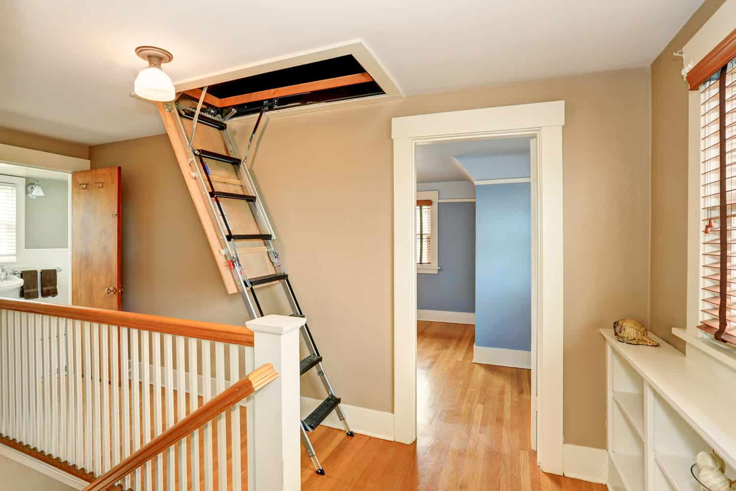 An attic ladder dropped down on a hallway of a rustic themed house