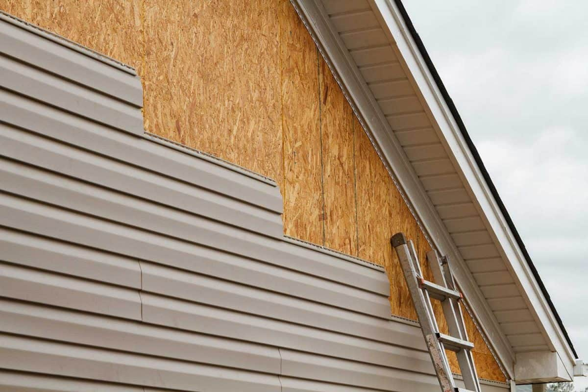 New beige vinyl siding being installed over an osb (oriented strand board) substrate on a residential house