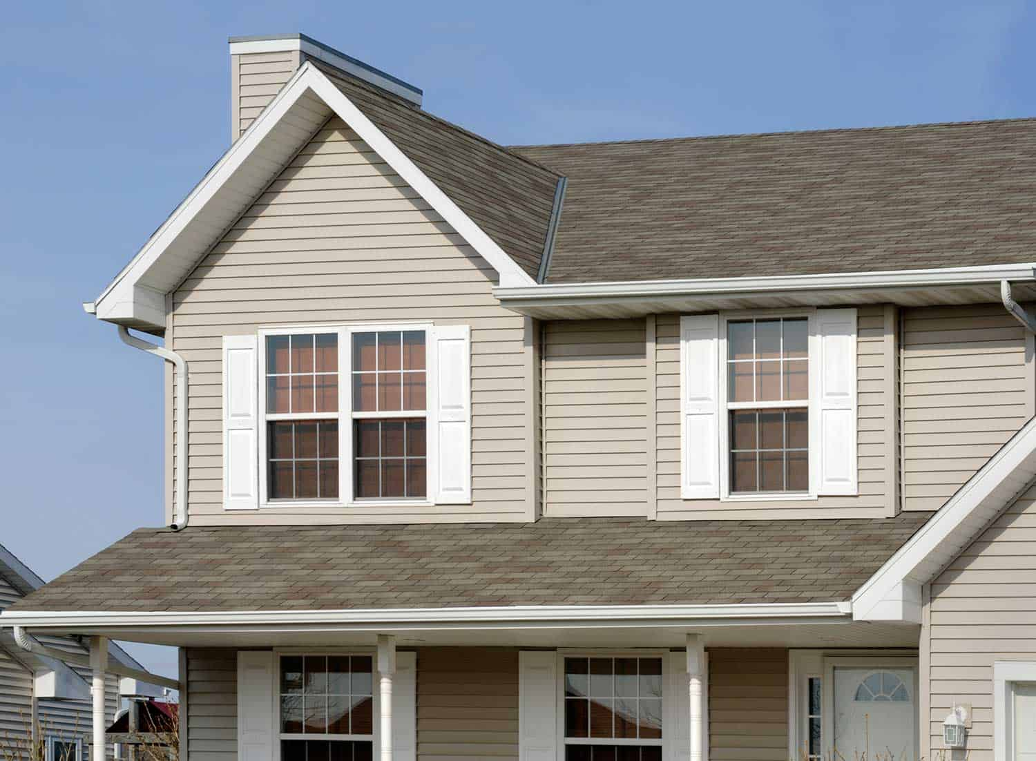 Residential home with vinyl siding, gable roof, seamless gutters and shutters