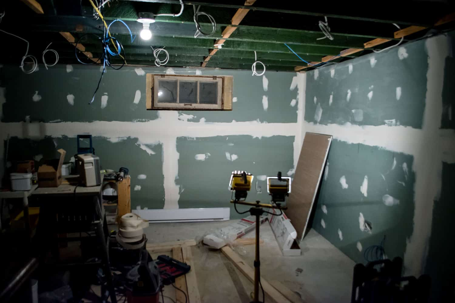 Unfinished basement with visible wires and unpainted drywall board sidings