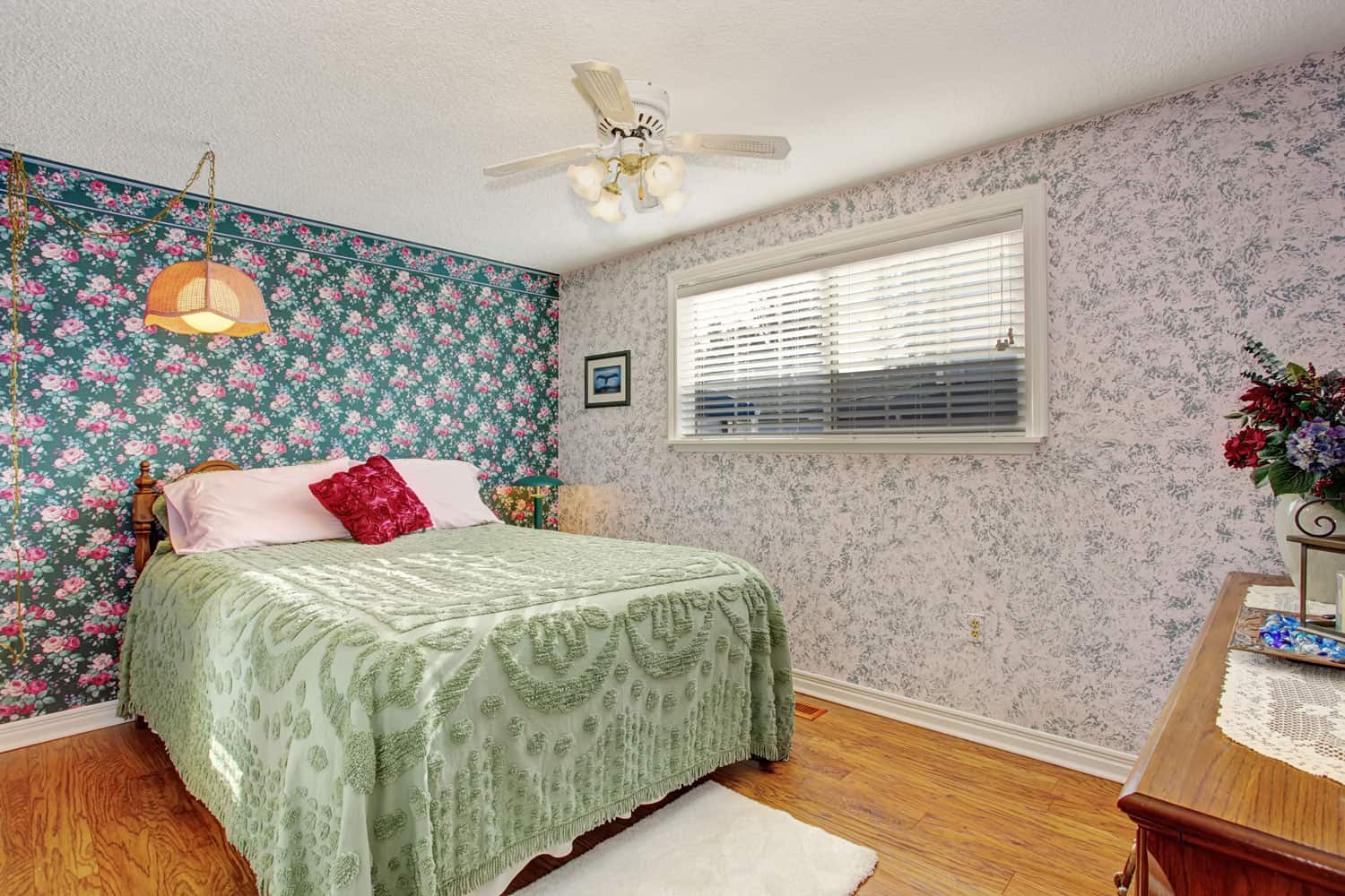 Floral themed basement bedroom with flora wallpapers, hardwood flooring, and green floral bedding