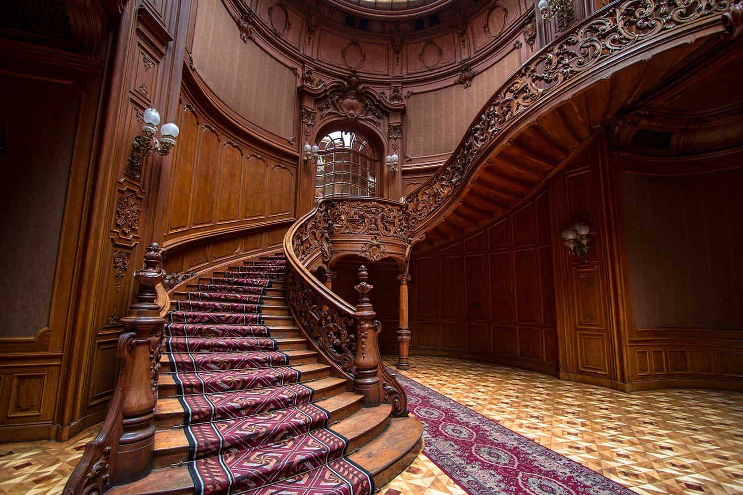 Rich entrance hall with stained-glass window, twisted staircase and laced rails