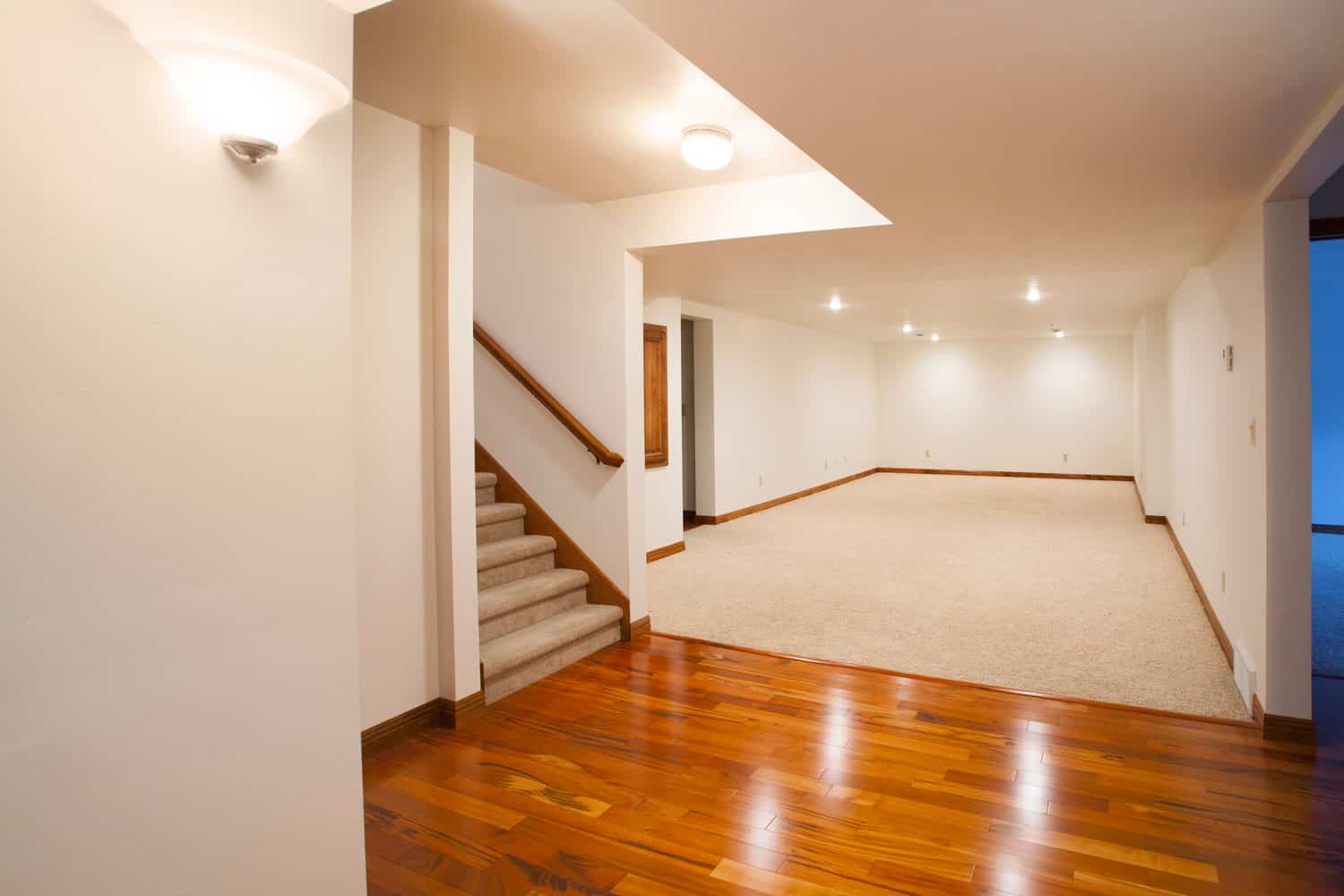 Interior of a modern basement with wooden laminated flooring and a section with carpeted flooring