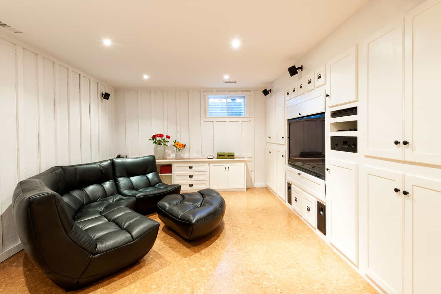 A black colored curved sectional sofa inside a white colored flat paneled basement