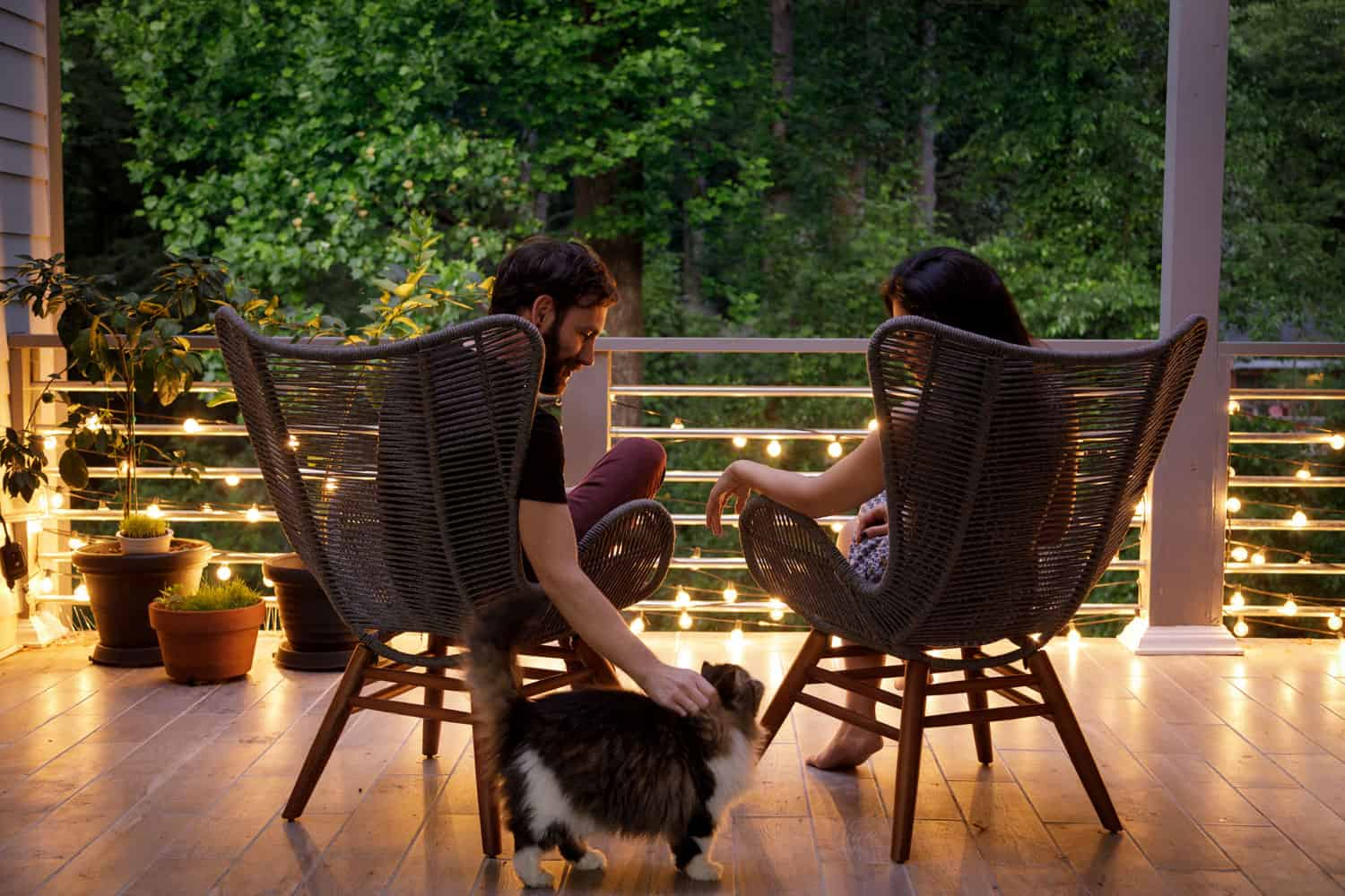 A couple sitting on the porch on a modern house
