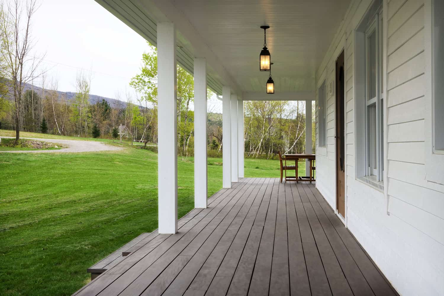 A front porch of a ranch style house with white painted sidings and a spacious newly mowed lawn