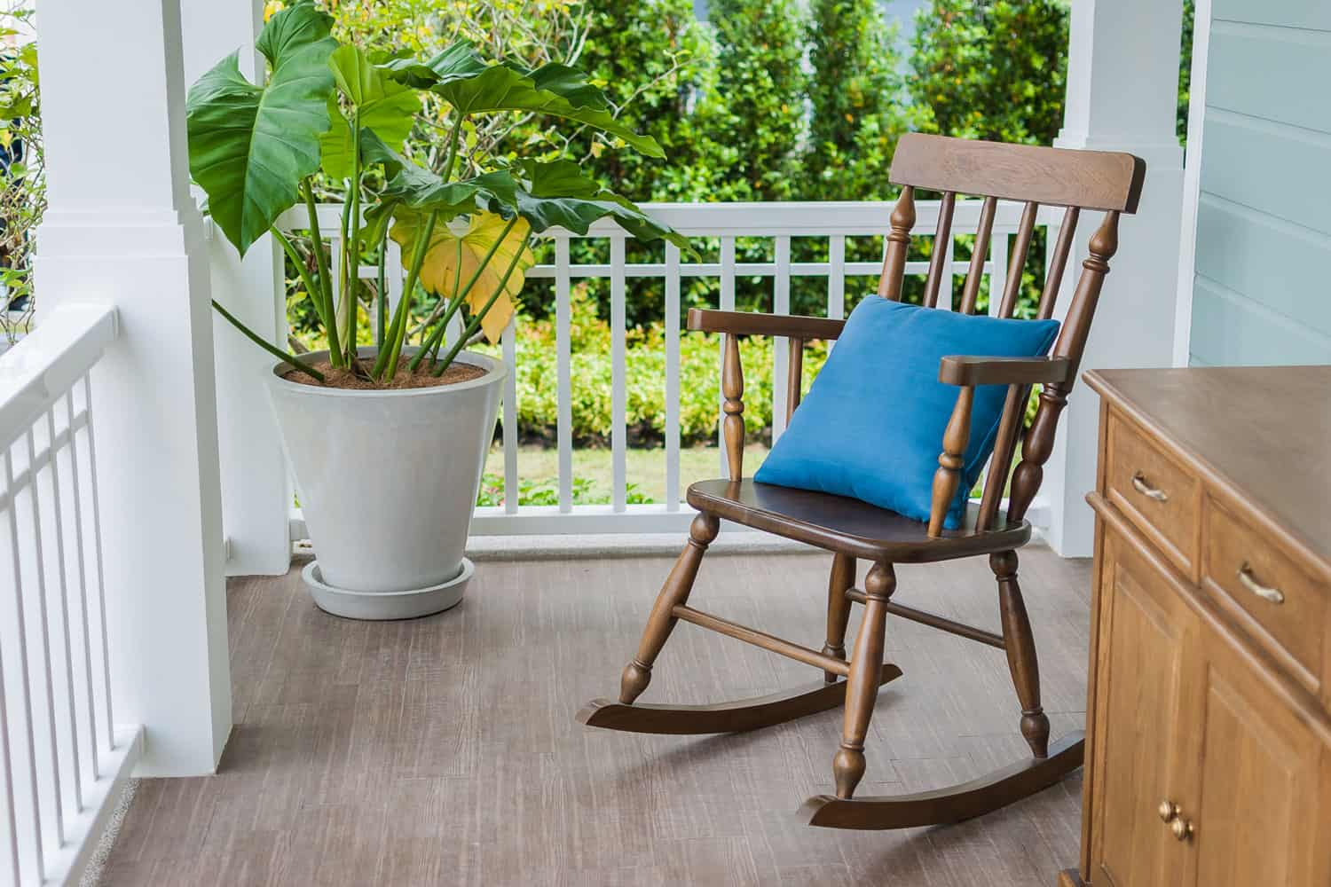 A front porch with wooden laminated flooring, a small wooden rocking chair, and a white painted porch fence