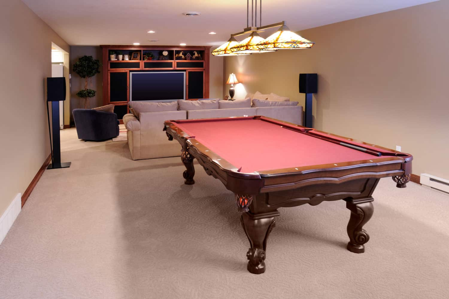 An entertainment area of a basement with carpeted flooring, beige colored walls, and a TV on the background
