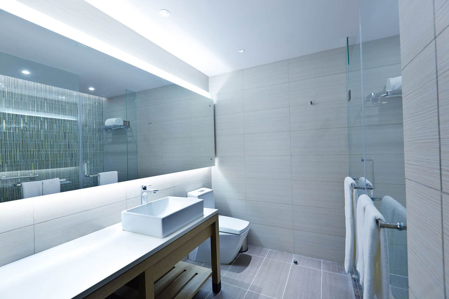Contemporary interior of a modern bathroom with long span mirror and a minimalst sink and granite countertop