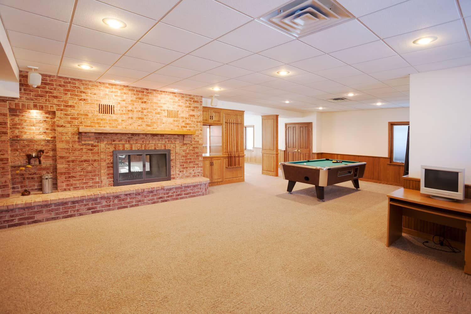 Interior of a spacious basement entertainment area with a brick wall and carpeted flooring