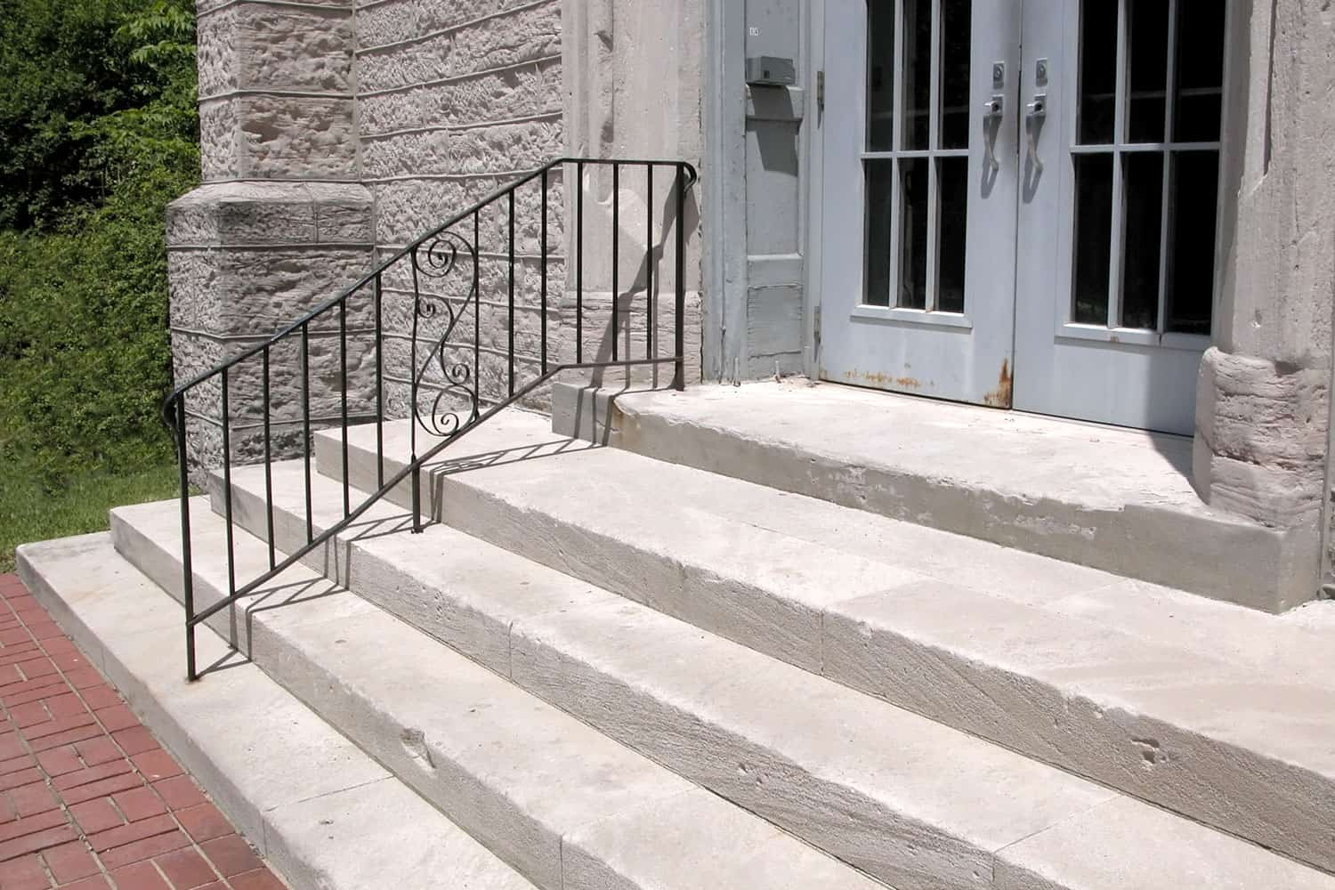 Limestone stairs and a metal railing leading to a light blue double door