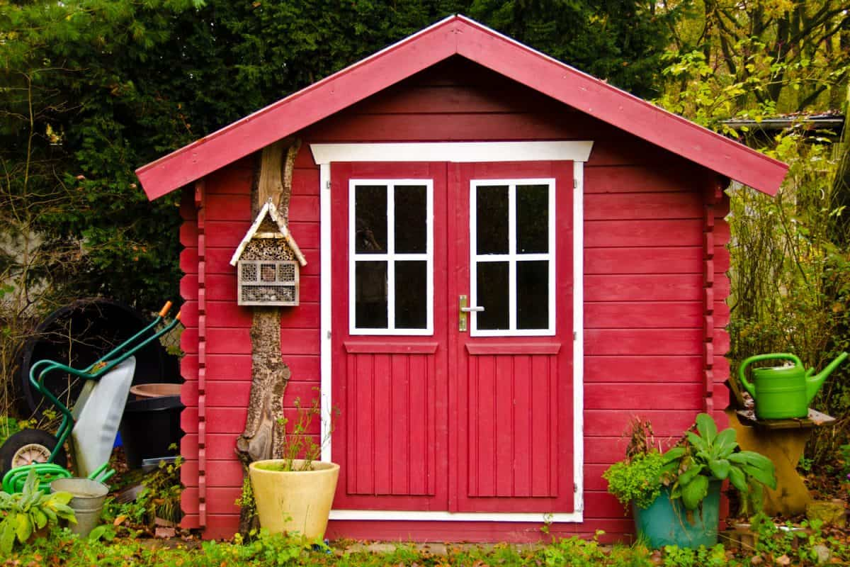 A bright yellow colored shed with white painted window and door frames