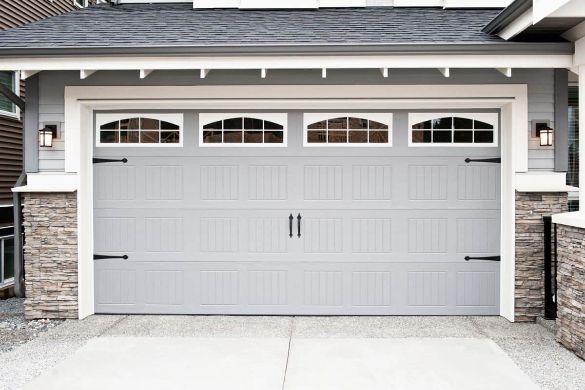 A brown colored garage door with arched windows, decorative stones, and gray shingle roofing