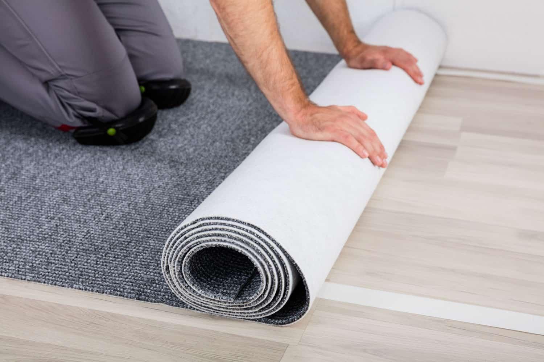 A carpet installer rolling a huge sheet of gray colored carpet