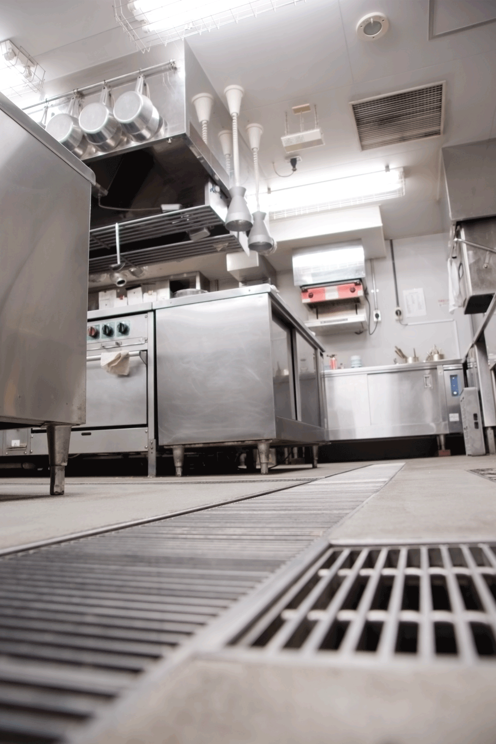 A clean restaurant kitchen before the operation hours, floor sink close up photo