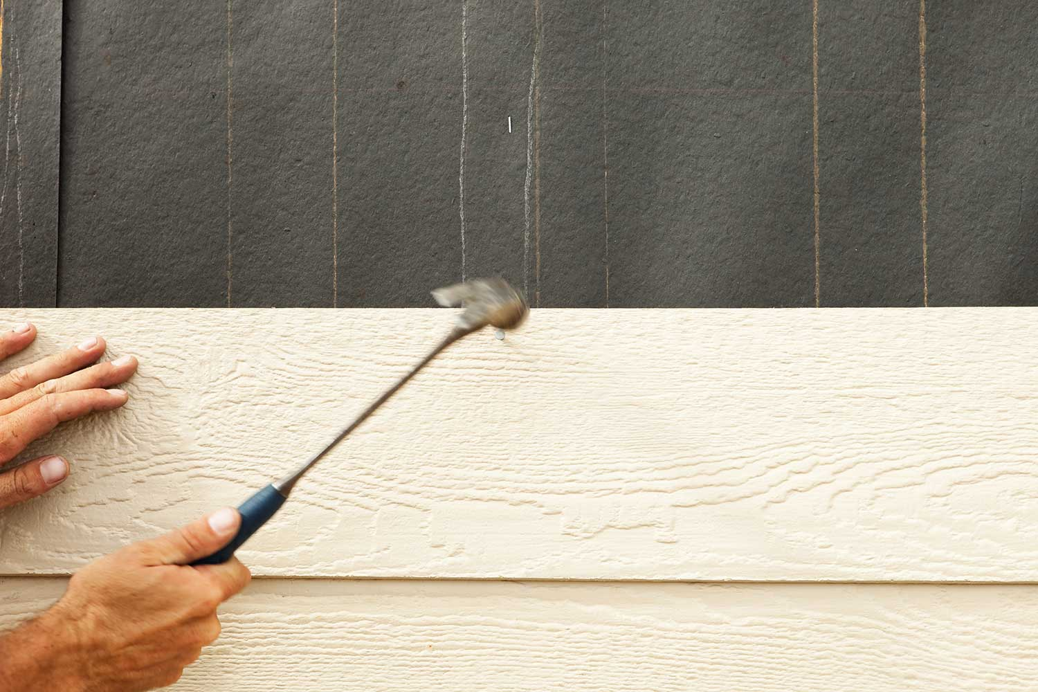 A construction worker using a hammer installing siding onto a tar paper covered exterior house wall