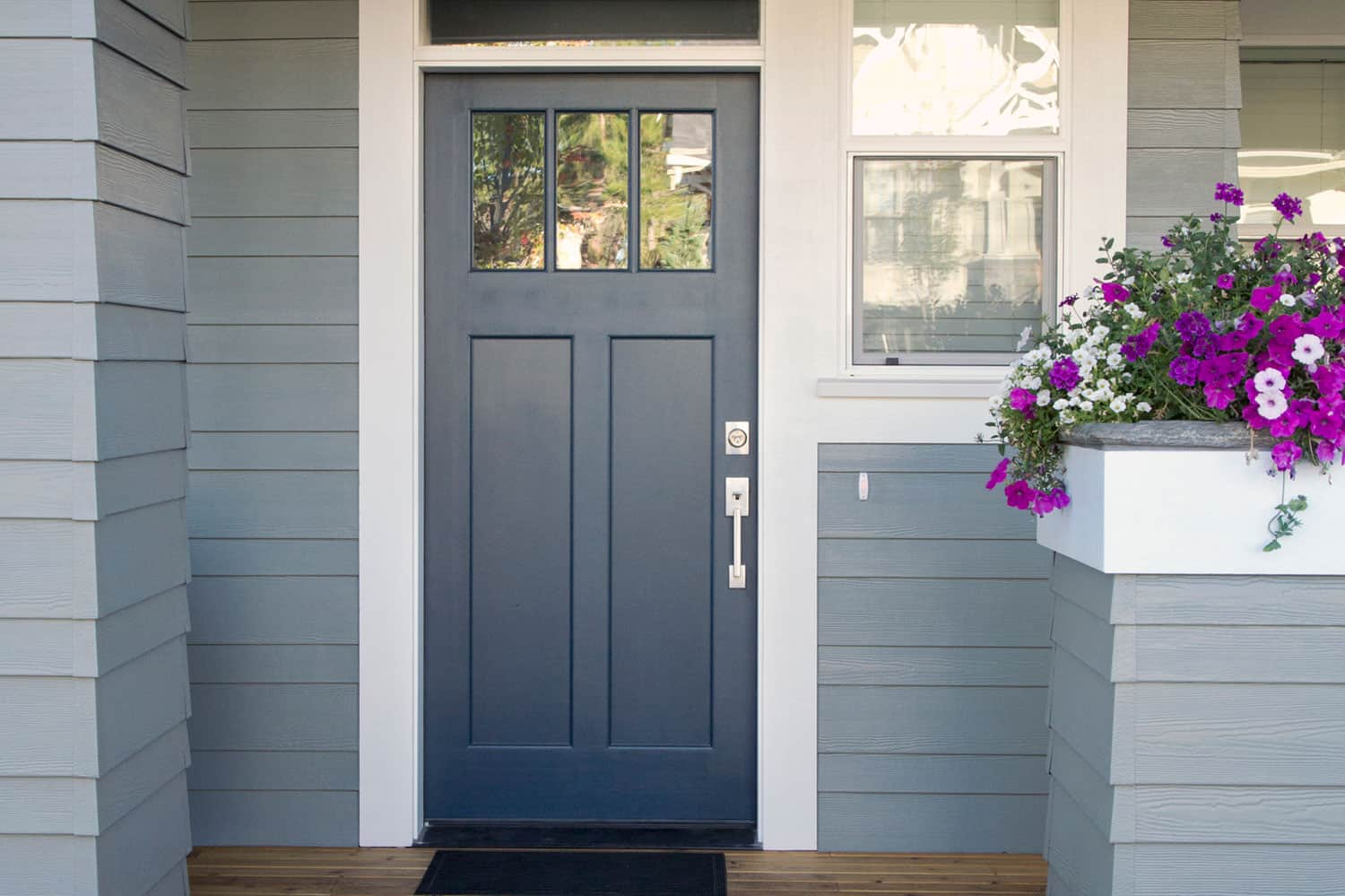 A gray front door of a home with front porch and flowers,What Color Door Knobs With Grey Doors?