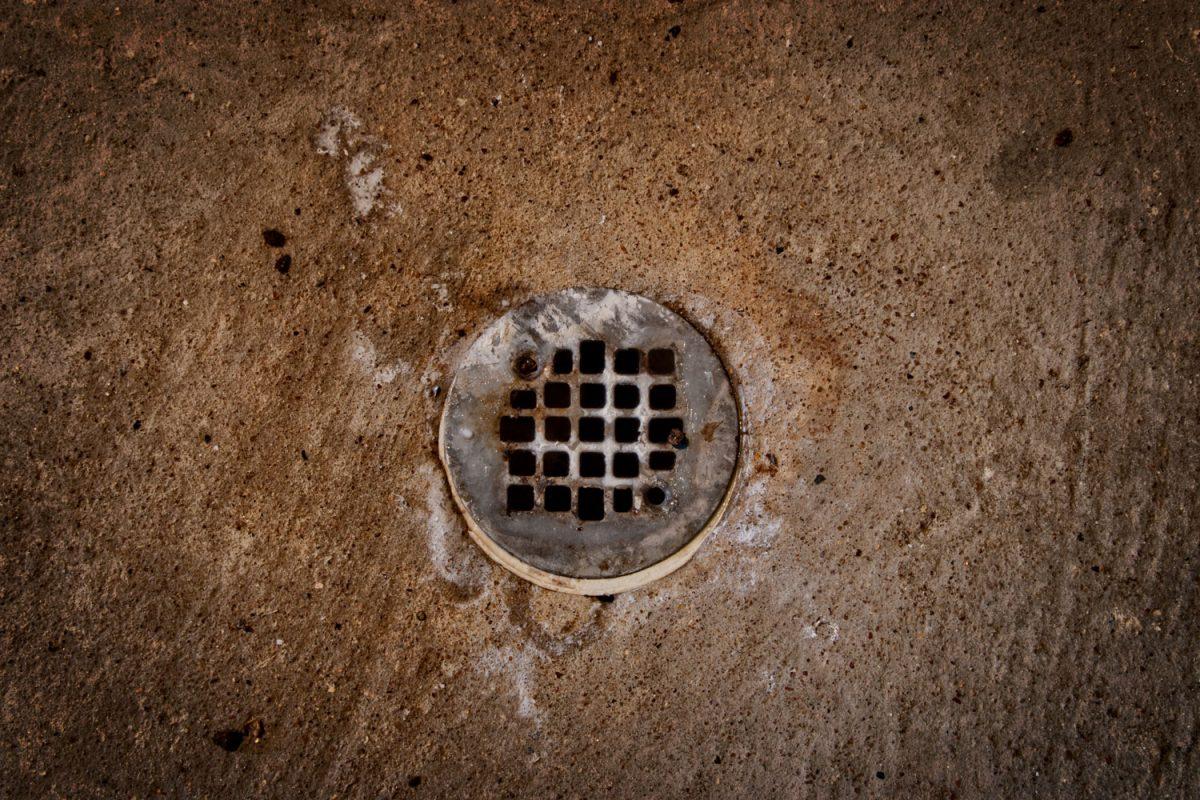 A rusty floor drain inside the bathroom